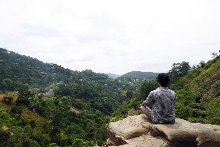 滝の側に座る